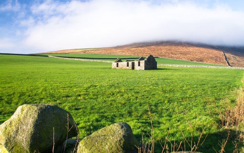Vecchia casa di pietra in un campo erboso, Irlanda del Nord fotografie stock