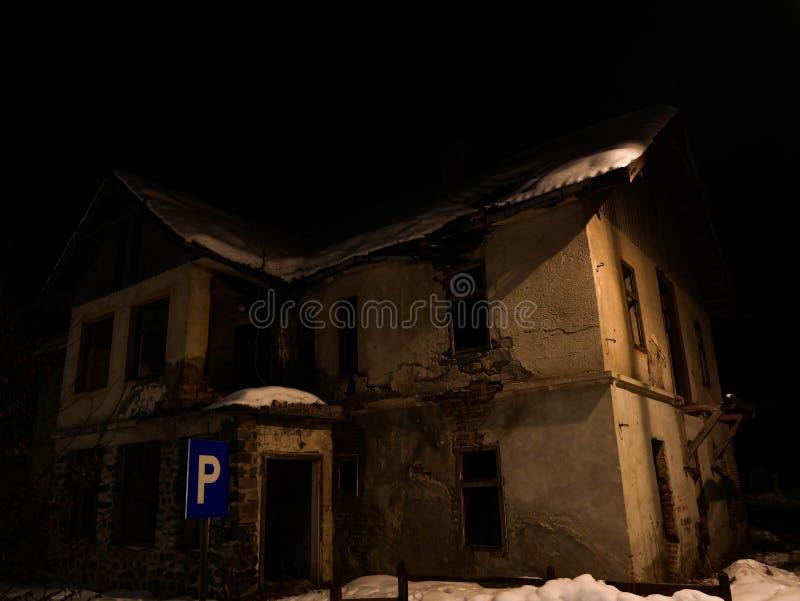 Vecchia, casa di sbriciolatura terrificante e abbandonata alla notte immagini stock