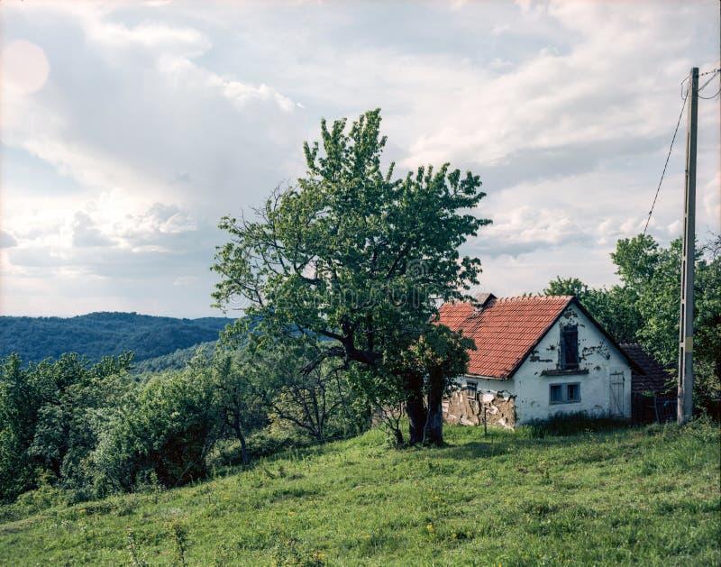 Vecchia casa nociva su una collina fotografia stock