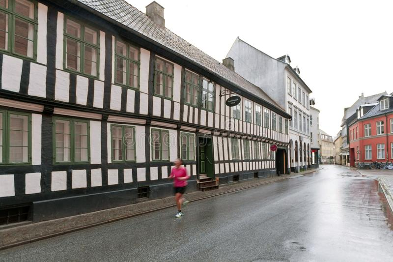 Vecchia casa rossa con le finestre bianche - casa a graticcio fatta di legno e dei mattoni Bicicletta vicino alla parete immagine stock libera da diritti