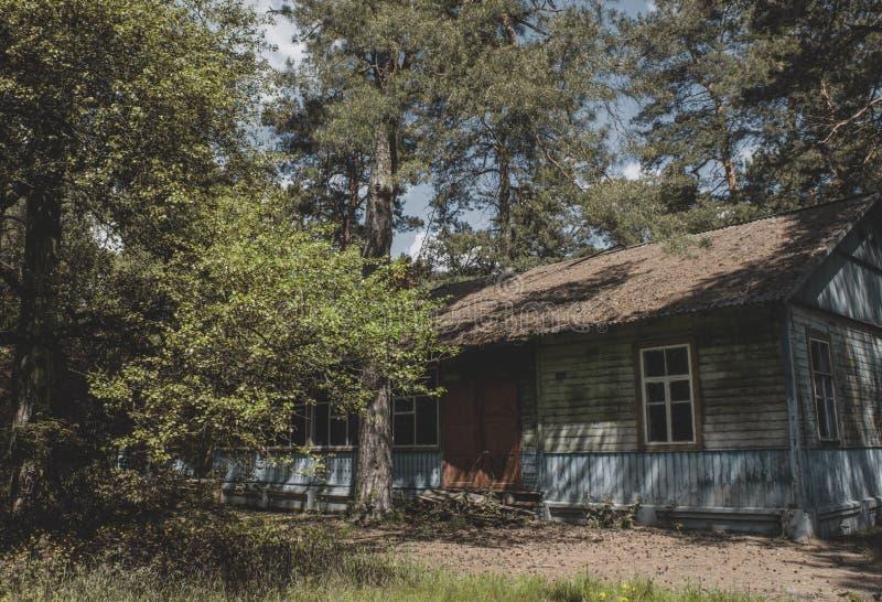 Vecchia casa spaventosa terrificante al campo abbandonato del campeggio estivo immagine stock
