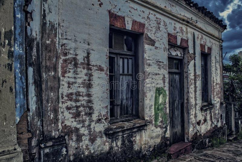 Vecchia casa sporca che va in pezzi al crepuscolo con il cielo nuvoloso fotografia stock libera da diritti