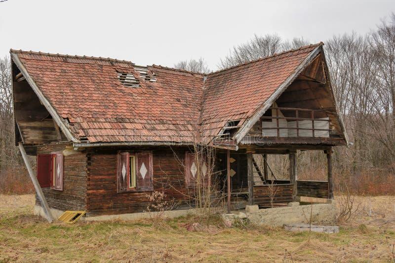 Vecchia casa sprofondante di legno abbandonata rurale contro il cielo nuvoloso nella stagione di autunno fotografia stock libera da diritti