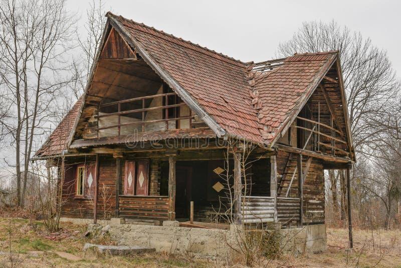 Vecchia casa sprofondante di legno abbandonata rurale contro il cielo nuvoloso nella stagione di autunno immagini stock