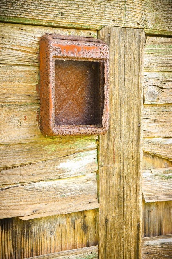 Vecchia cassetta delle lettere rossa contro una porta di legno fotografia stock