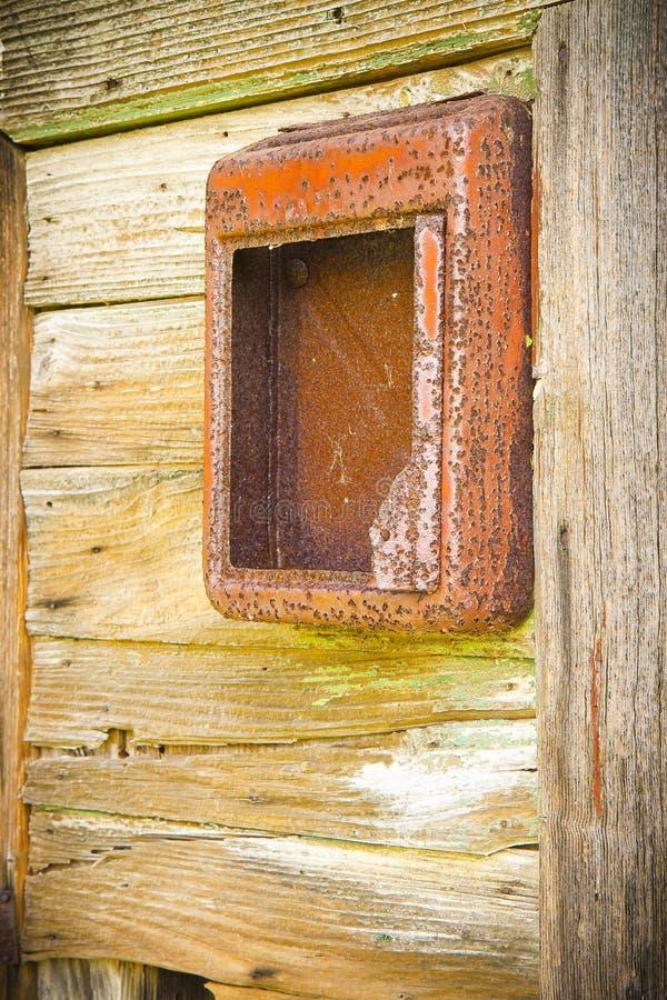 Vecchia cassetta delle lettere rossa contro una porta di legno fotografie stock