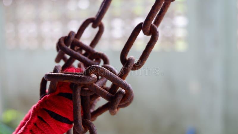 Vecchia catena arrugginita con la corda rossa per l'amaca fotografie stock libere da diritti