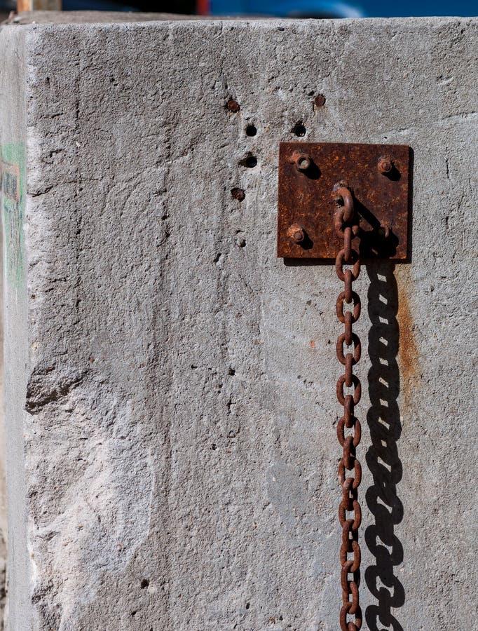 Vecchia catena pesante arrugginita che appende lungo la parete fotografia stock