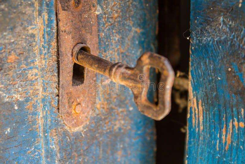 Vecchia chiave arrugginita e buco della serratura su una porta di legno blu fotografie stock libere da diritti