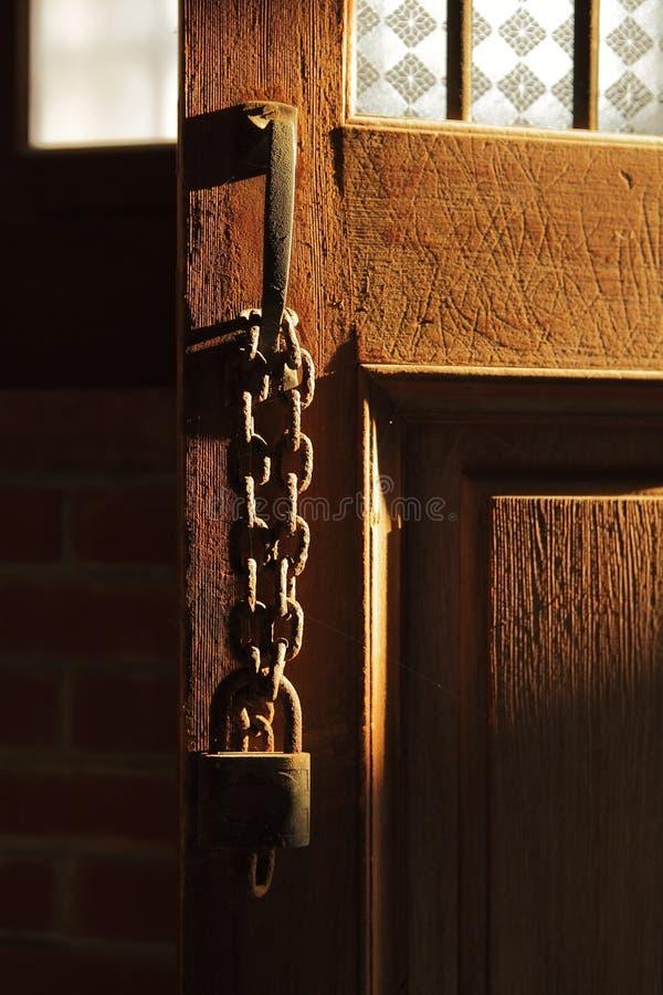 Vecchia chiave di catenaccio sul portello di legno immagini stock