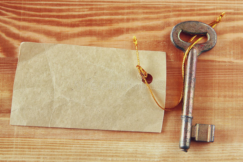 Vecchia chiave t con l'etichetta o l'etichetta sopra fondo strutturato di legno fotografia stock
