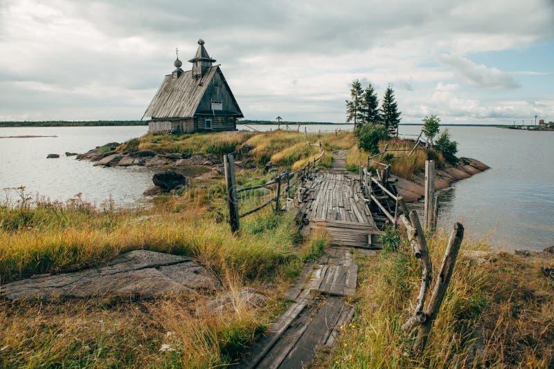 Vecchia chiesa di legno ortodossa russa nel villaggio Rabocheostrovsk, Carelia Chiesa abbandonata sulla linea costiera immagini stock libere da diritti