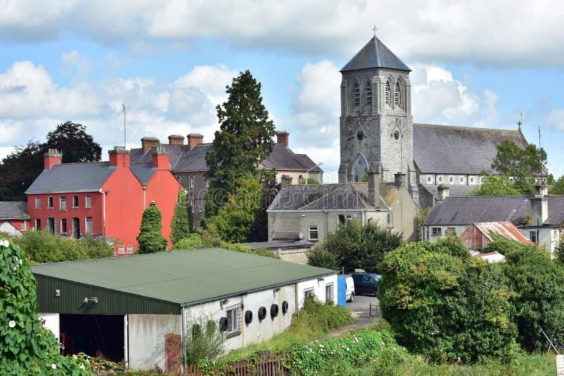 Vecchia chiesa di pietra dietro i fabbricati industriali fotografie stock