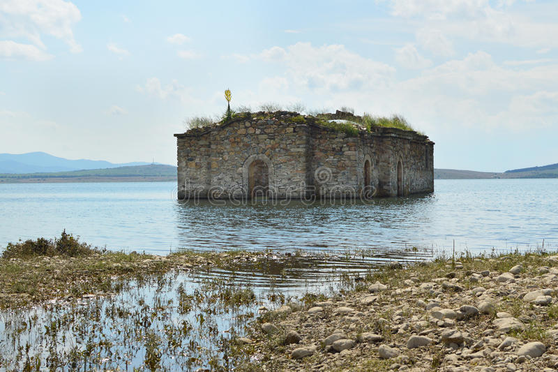 Vecchia chiesa inghiottita nell'acqua del lago della diga immagine stock