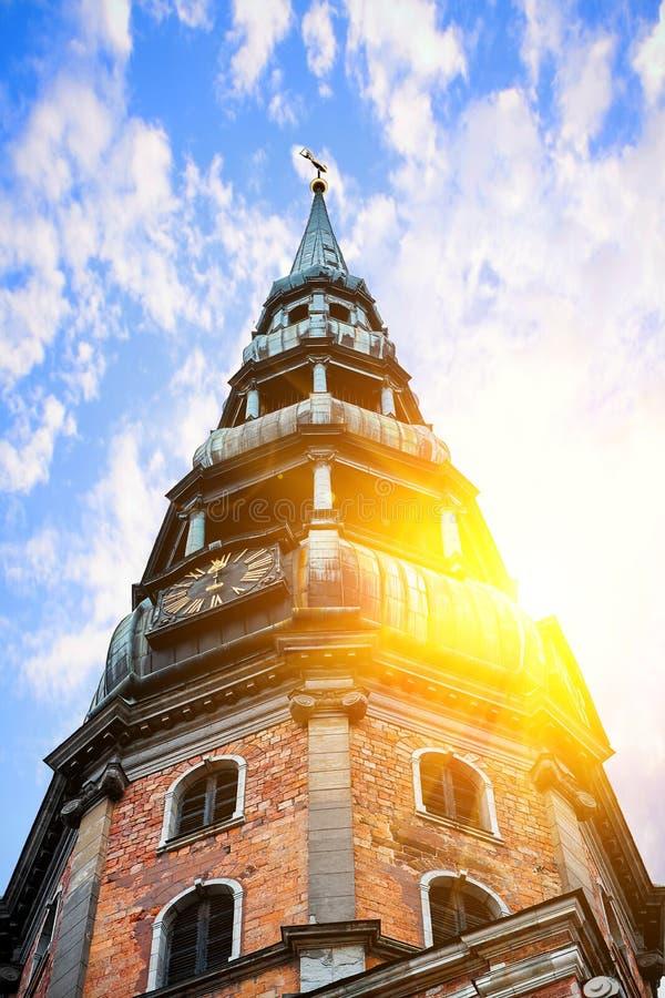 Vecchia chiesa medievale di Peters Lutheran del san a Riga, Lettonia contro il cielo nuvoloso blu il giorno soleggiato luminoso fotografie stock