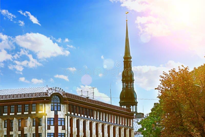 Vecchia chiesa medievale di Peters Lutheran del san a Riga, Lettonia contro il cielo nuvoloso blu il giorno soleggiato luminoso immagini stock