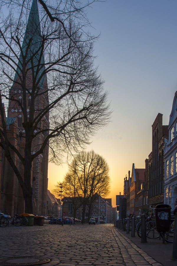 Vecchia città con le vie cobbled e una chiesa in Europa al tramonto fotografia stock