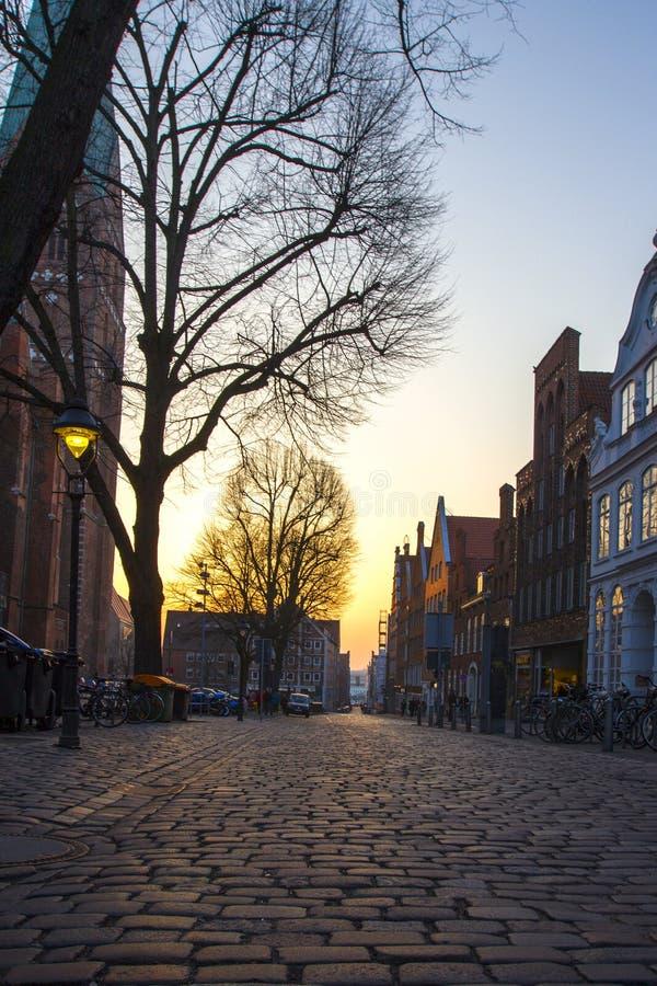 Vecchia città con le vie e gli alberi cobbled in Europa al tramonto immagine stock