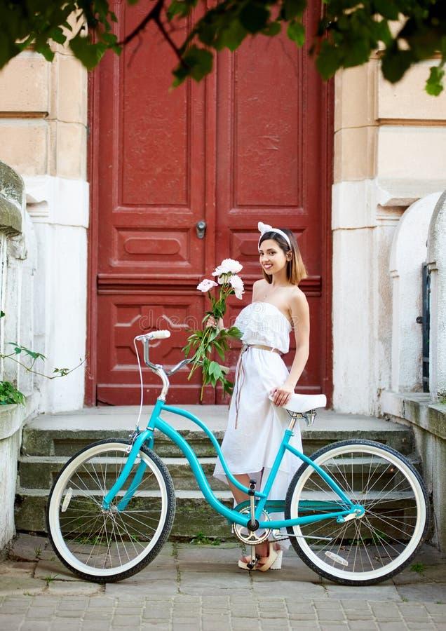 Vecchia città Ragazza adorabile con le retro peonie del mazzo e della bicicletta fotografie stock