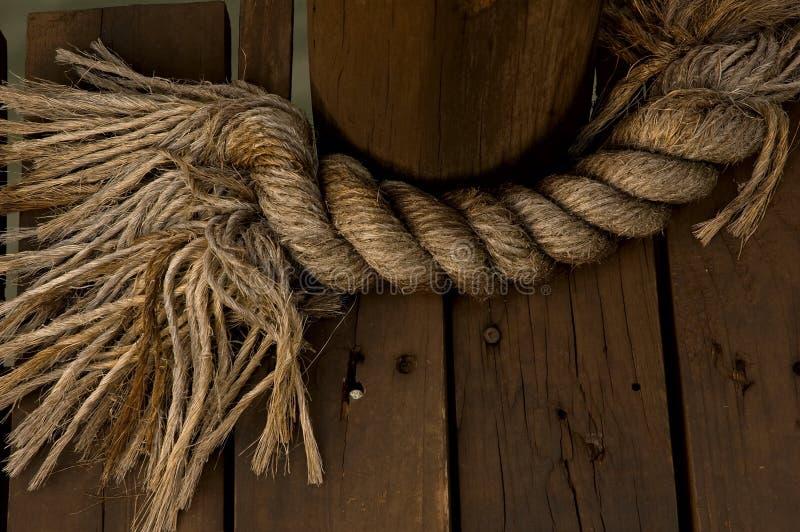 Vecchia corda legata sulla piattaforma di legno immagini stock