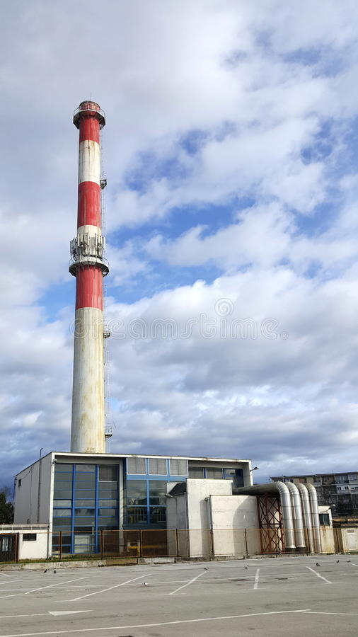 Vecchia costruzione della centrale elettrica con l'alto camino industriale fotografia stock