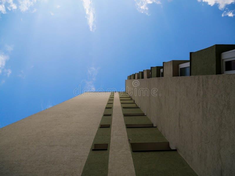 Vecchia costruzione di appartamento ricondizionata contro il cielo blu immagine stock