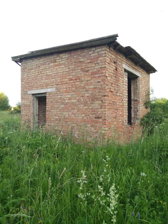 Vecchia costruzione di mattone abbandonata in un campo contro il cielo un giorno di estate immagini stock libere da diritti