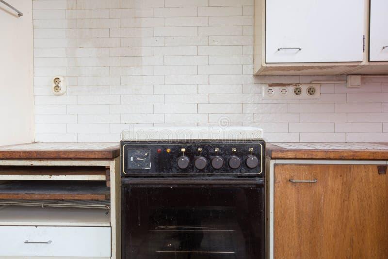 Vecchia cucina antica arrugginita con il forno sporco immagini stock