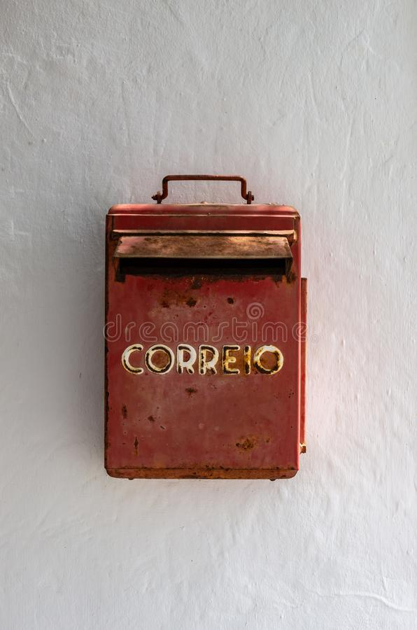 Vecchia e cassetta delle lettere rossa arrugginita in una parete bianca fra un albero e una porta fotografia stock