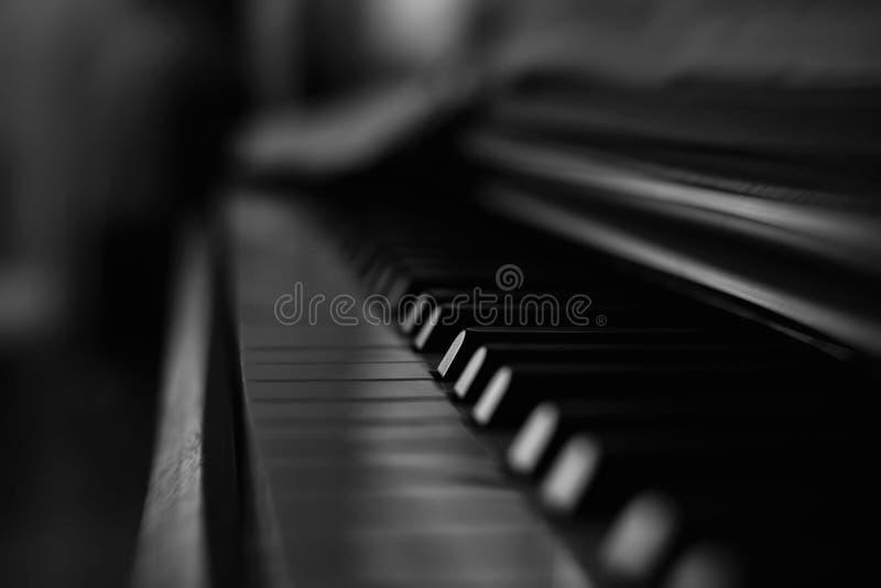 Vecchia e tastiera di piano in bianco e nero di legno nei darknes con musica fotografia stock