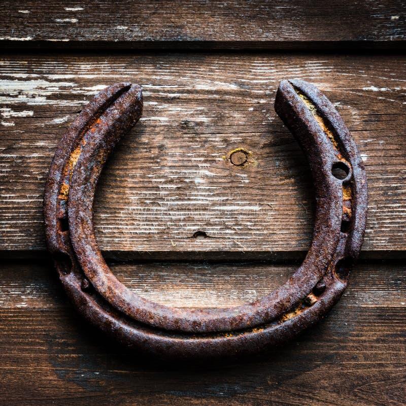Vecchia ed attaccatura arrugginita fortunata del ferro di cavallo, sul granaio fotografie stock libere da diritti