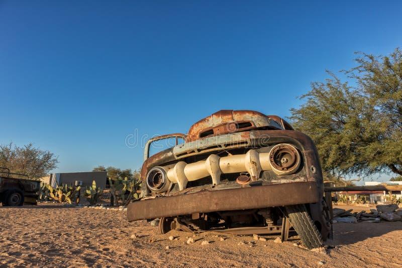 Vecchia ed automobile abbandonata nel deserto della Namibia solitaire Con la bella luce dell'alba immagine stock