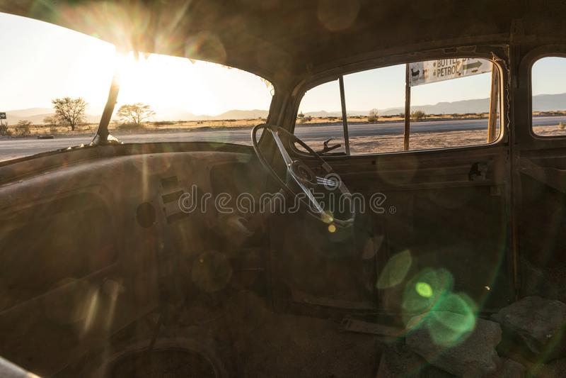 Vecchia ed automobile abbandonata nel deserto della Namibia solitaire Con la bella luce dell'alba Vista interna fotografia stock libera da diritti