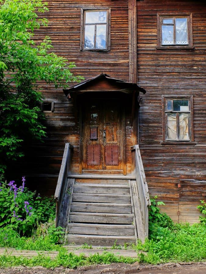 Vecchia entrata di legno della casa circondata da erba e dagli alberi immagini stock libere da diritti