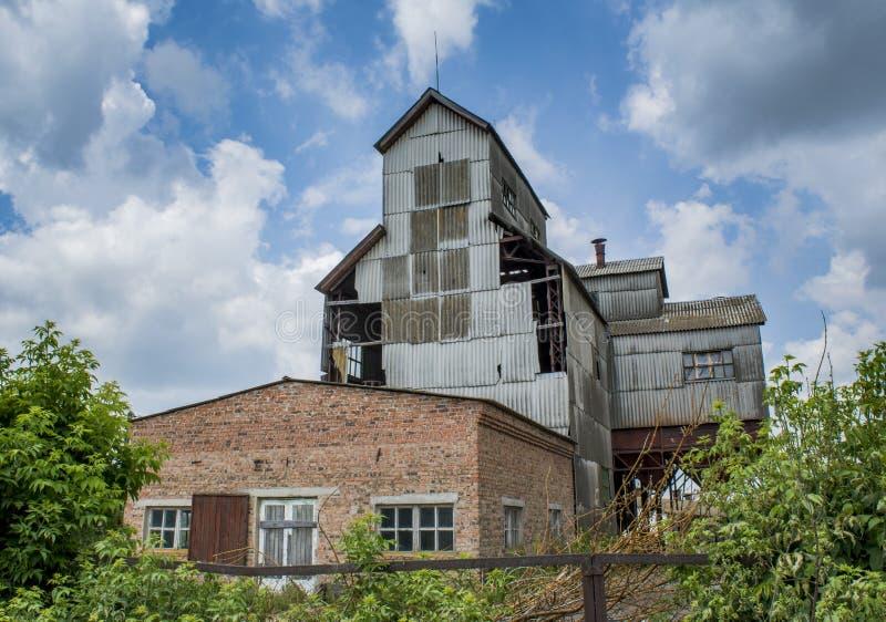 Vecchia fabbrica spaventosa abbandonata del grano nel villaggio dimenticato immagini stock