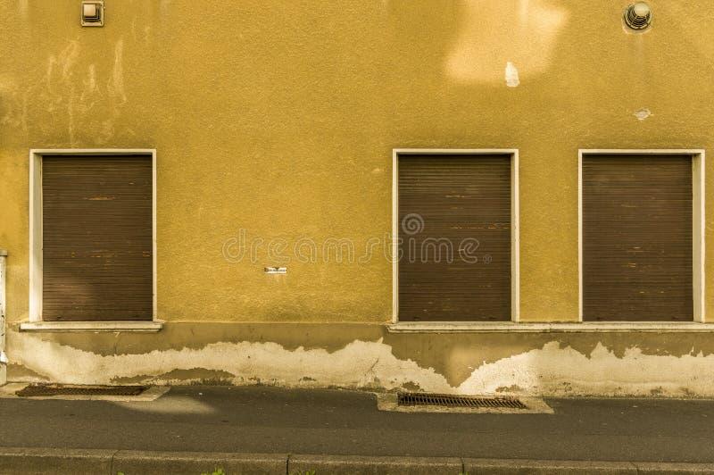 Vecchia facciata con 3 otturatori di legno marroni di una casa con il marciapiede immagini stock libere da diritti