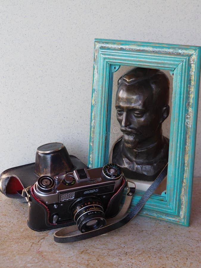 Vecchia federazione della macchina fotografica con una statua bronzea di Felix Edmundovich Dzerzhinsky nel telaio di legno della  fotografie stock