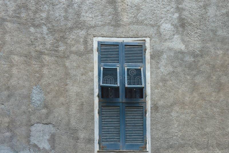 Vecchia finestra di legno blu con gli otturatori sulla parete misera grigia di una casa italiana fotografie stock