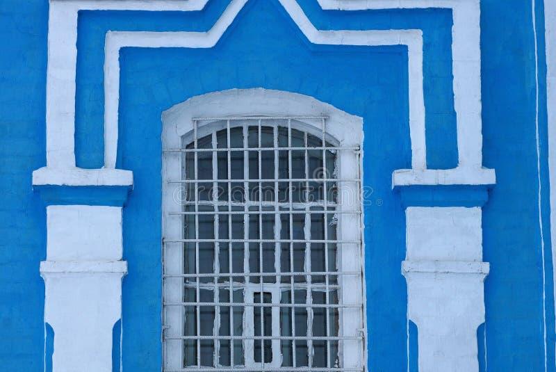 Vecchia finestra dietro le sbarre di ferro su una parete bianca blu del mattone immagine stock