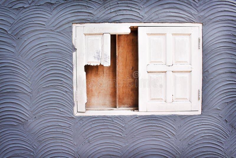 Vecchia finestra rotta bianca su struttura del muro di cemento nei modelli approssimativi senza cuciture dell'onda per fondo immagine stock