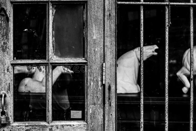 Vecchia finestra sporca di una casa abbandonata con il fuoco sulla lastra di vetro fracassata immagini stock