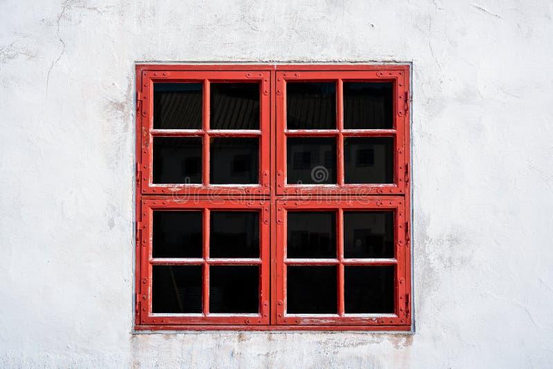 Vecchia finestra stagionata rossa con i quadrati sulla parete bianca con struttura consumata fotografie stock libere da diritti