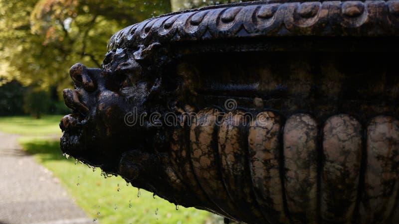 Vecchia fontana di pietra con il fronte immagini stock