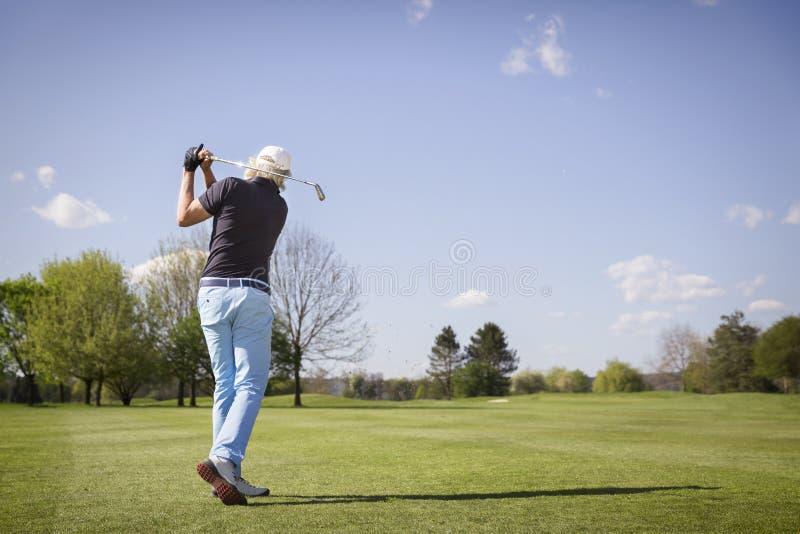 Vecchia fucilazione del giocatore di golf sul verde fotografie stock libere da diritti