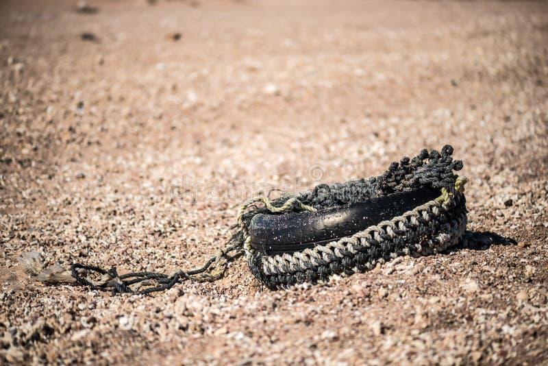 Vecchia gomma di automobile sulla sabbia in deserto fotografie stock