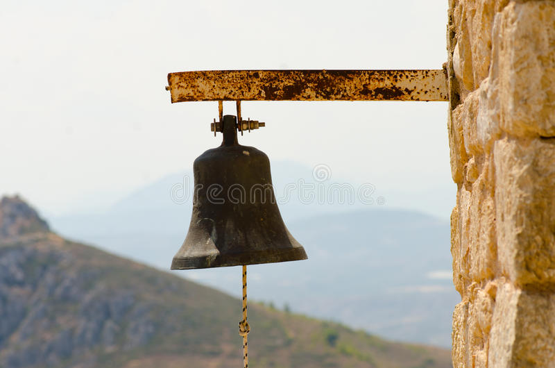 Vecchia grande campana d'acciaio arrugginita dalla chiesa con la corda sulla parete di pietra dentro fotografia stock libera da diritti