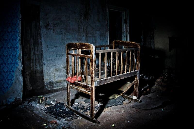 Vecchia greppia di legno sinistra terrificante del bambino in casa abbandonata Concetto di orrore fotografie stock