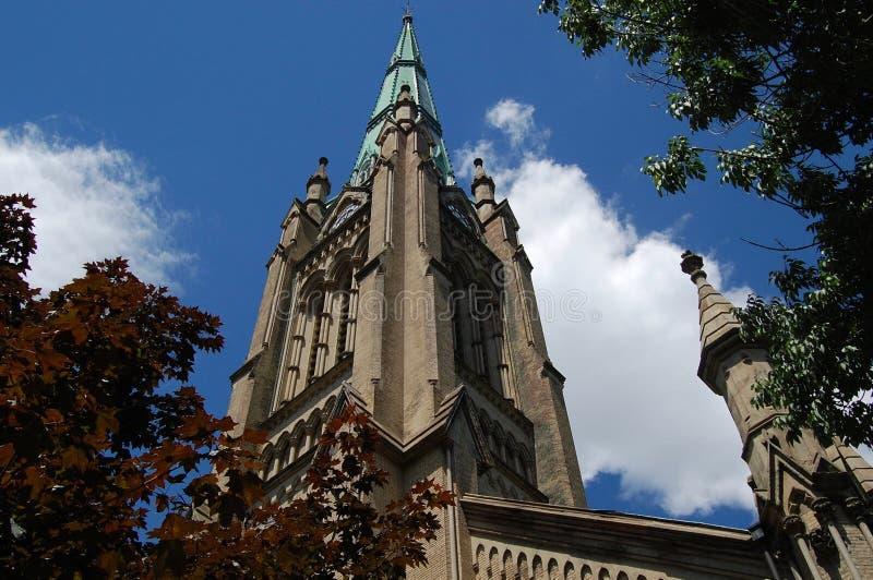 Vecchia guglia della cattedrale che raggiunge nel cielo blu e nelle nuvole bianche incontaminate fotografia stock libera da diritti