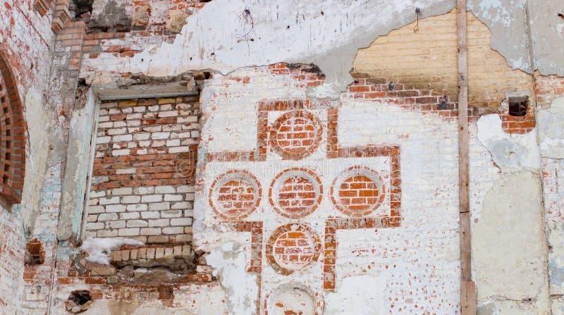 Vecchia immagine di un incrocio cristiano in un muro di mattoni fotografia stock