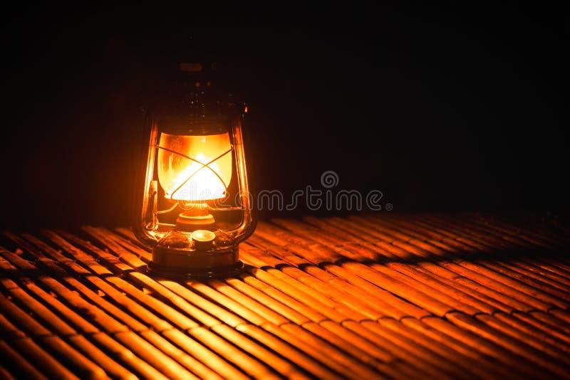 Vecchia lampada bruciante del cherosene su di legno di bambù, accendendosi nel campeggio alla notte immagine stock libera da diritti